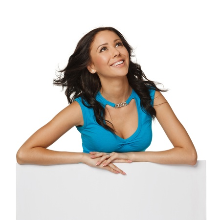 Smiling happy woman standing behind and leaning on a white blank billboard   placard, looking to the side, over white background photo