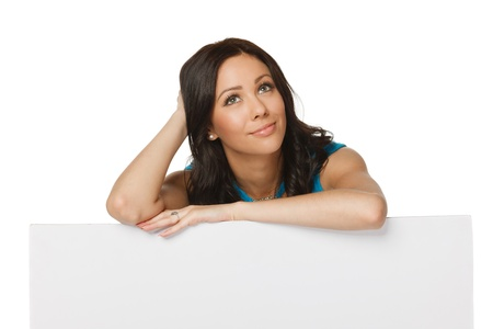 Pensive woman standing behind and leaning on a white blank billboard   placard, looking to the side, over white background photo