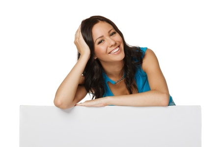 Smiling happy woman standing behind and leaning on a white blank billboard   placard, over white background photo