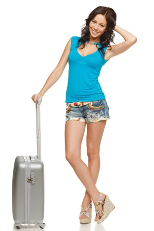 denim shorts: Full length of casual female standing with travel suitcase, isolated on white background