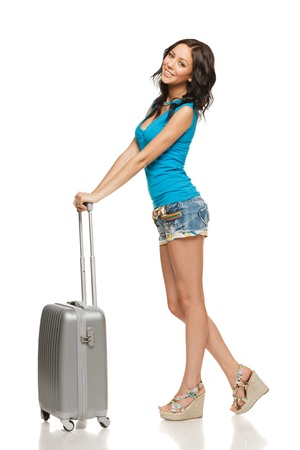 Full length of casual female standing with travel suitcase, isolated on white background photo