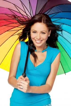 Beautiful young female standing under rainbow umbrella against white background photo