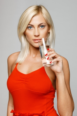 Portrait of a pretty young woman in bright red dress holding a glass of water, over gray background photo