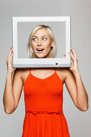 Surprised young blond female looking through the TV   computer screen frame, looking to the side, over gray background photo