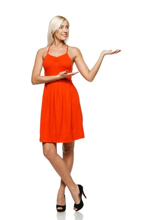 Full length of young trendy woman in bright red dress showing a product - empty copy space on the open hand palm, looking at the copy space on her palm, over white background