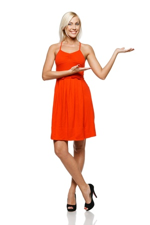 casual dress: Full length of happy young woman showing a product - empty copy space on the open hand palm, over white background