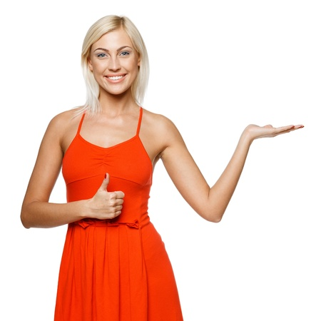 casual dress: Happy young woman showing a product - empty copy space on the open hand palm, showing thumb up sign, over white background