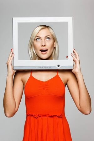 Surprised young blond female looking through the TV  computer screen frame, looking up, over gray background photo