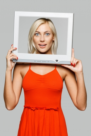 Surprised young blond female looking through the TV   computer screen frame, over gray background photo