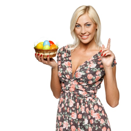 Closeup of happy female holding basket with Easter eggs with her finger up, isolated on white background Stock Photo - 15362229