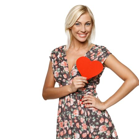 Young blond female in summer dress holding red heart shape near her heart isolated on white background photo