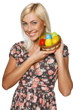 Portrait of happy female holding basket with Easter eggs, isolated on white background photo