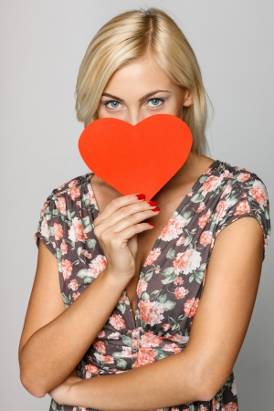 Young beautiful female in summer dress peeking from the red heart shape isolated on gray background Stock Photo - 15333879