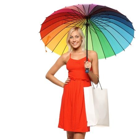 sotto la pioggia: Giovane donna in abito rosso brillante in piedi sotto l'ombrello arcobaleno e tenendo shopping bag, su sfondo bianco