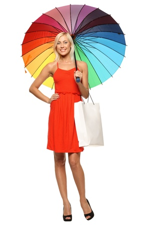 Full length of young female in bright red dress standing under rainbow umbrella and holding shopping bag, over white background photo