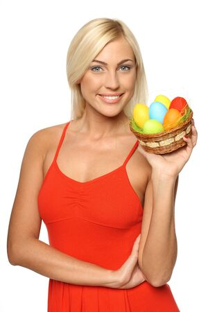 Smiling female in bright red dress holding basket with Easter eggs, looking at camera, isolated on white background