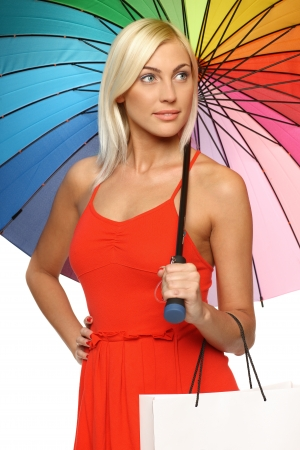Relaxed young female in bright red dress standing under rainbow umbrella and holding shopping bag, looking to the side Stock Photo - 15416328