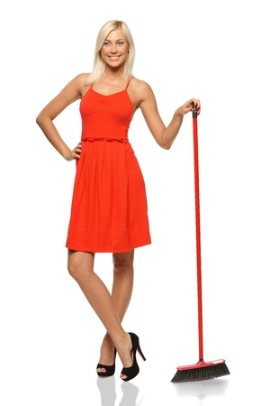 Full length of smiling woman standing with broom, looking to the side, isolated on white background Stock Photo
