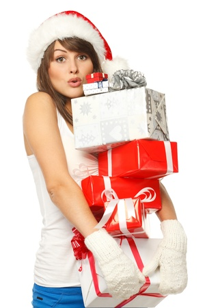 Christmas shopping woman with funny expression holding many gift boxes over white background. photo