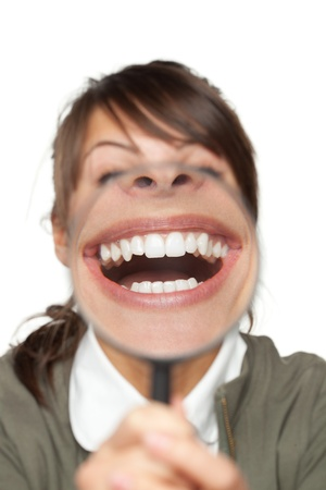 Funny image of female with magnifying glass showing teeth over white background