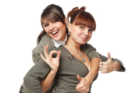 Two excited girls showing OK signs, isolated on white background photo