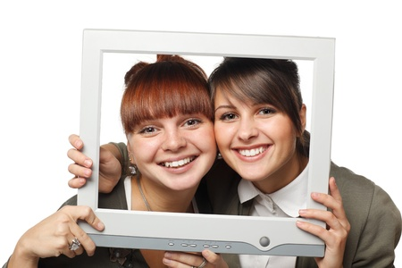 Two excited girls looking through the old fashioned computer screen, isolated on white background photo