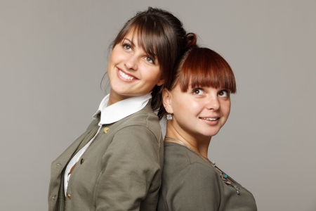 Closeup of two smiling girls standing back to back looking upwards, over grey background photo