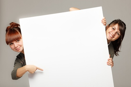 hands behind head: Two young women peeking over edge of blank empty paper billboard with copy space for text, over grey background