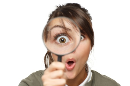 woman searching: Funny image of young surprised female looking at the camera through a magnifying glass, isolated on white background