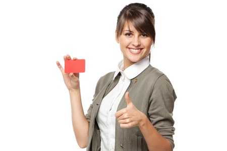 Close-up portrait of young smiling business woman holding credit card and showing tumb up sign isolated on white background
