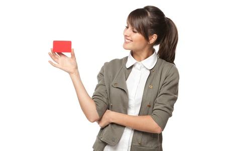 tarjeta de credito: Retrato de primer plano de la joven mujer de negocios sonriente que sostiene la tarjeta de cr�dito y y mirando a ella aislados en fondo blanco