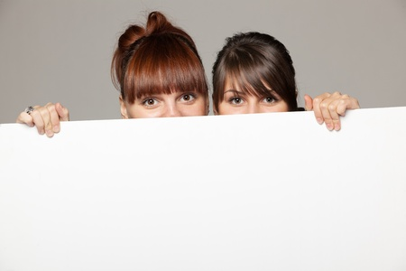 Two young women peeking over edge of blank empty paper billboard with copy space for text, over grey background photo