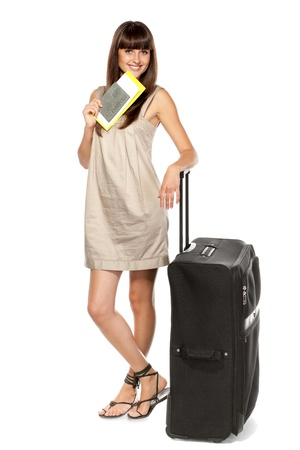 Full-body portrait of young female in dress with passport, tickets and suitcase going on holidays isolated on white background photo