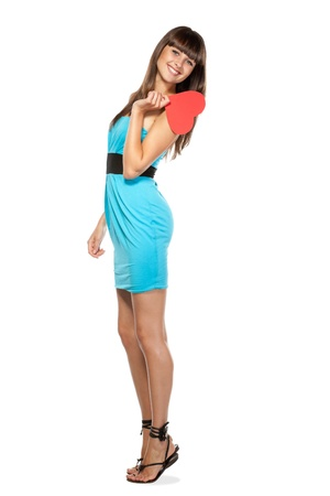 Full-body portrait of young female in blue dress holding heart shape isolated on white background photo
