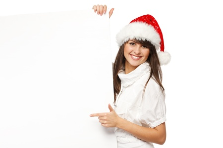 Smiling girl in Santa hat holding blank banner and pointing at it, isolated on white background photo