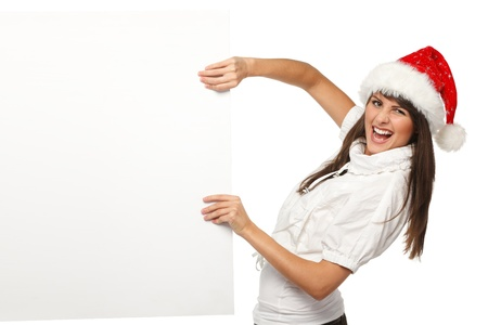 Funny image of young female wearing Santa hat pulling out a blank billboard with copy space applying effort, isolated on white background photo