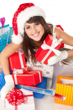 High angle view of young woman wrapping christmas presents wearing santa hat, shallow deep of field  photo