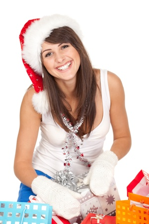 High angle view of young woman sitting with christmas presents wearing santa hat, shallow deep of field  photo