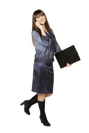 Full length of businesswoman walking talking on mobile phone, isolated on white background photo