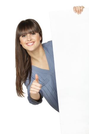 Young female holding the blank board and showing thumb up sign, isolated on white background photo