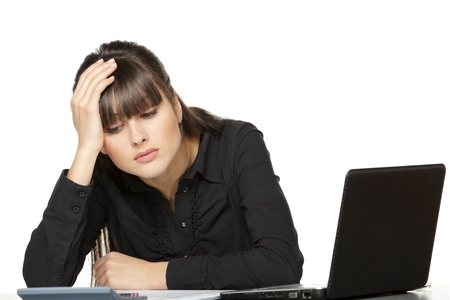 computer problem: Business woman with head in hands, looking at calculator exhausted, over white background