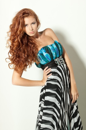 Beautiful redheaded fashion model posing in chiffon dress photo