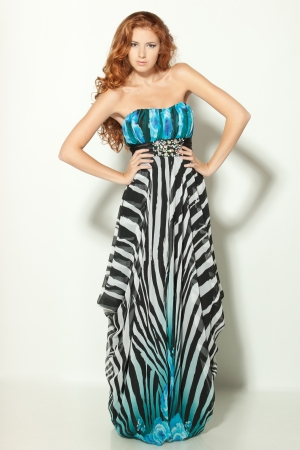 Full length of a beautiful redheaded fashion model posing in long chiffon dress photo