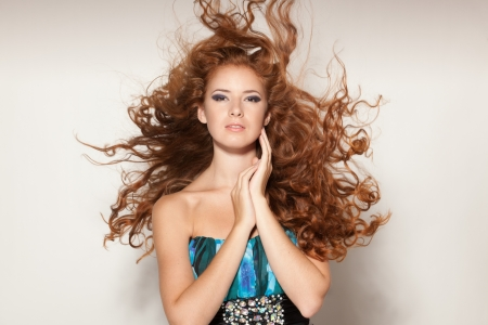 Fine art fashion portrait of red-haired fashion model posing with hair fluttering in the wind photo