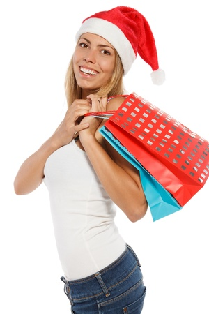 Happy woman in Santa hat holding shopping bags, over a white background. Stock Photo - 16031220