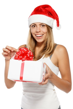 Happy excited woman in Santa hat unwrapping a Xmas gift, isolated on white background Stock Photo - 16031333