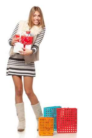 Full length of young female holding a heap of gifts, isolated on white background photo