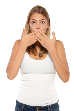 Close-up portrait of surprised  female covering her mouth by the hands, over white background photo