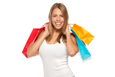 Young happy female holding shopping bags with purchases over white background photo