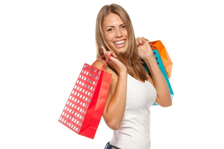 Side view of young happy female holding shopping bags with purchases over white background photo